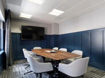 Modern refurbished office meeting room with navy panelled walls and large central table