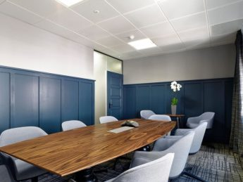 Newly fit out office meeting room with blue panelled walls and dark wood table