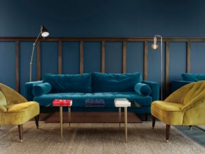 Velvet sofa seating area with blue panelled walls