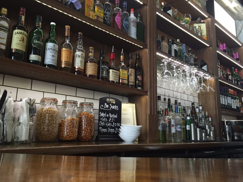 Alcoholic drinks and glasses behind the bar at a London pub