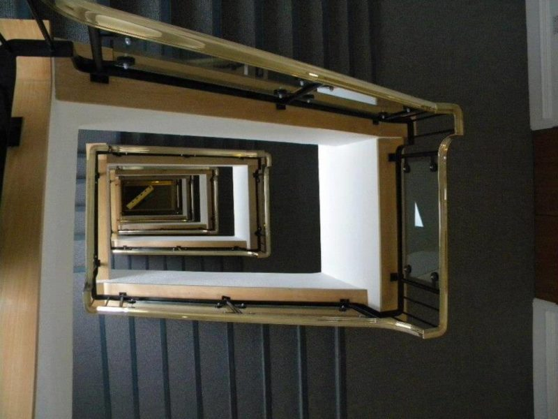 Refurbished residential stairwell with gold bannister
