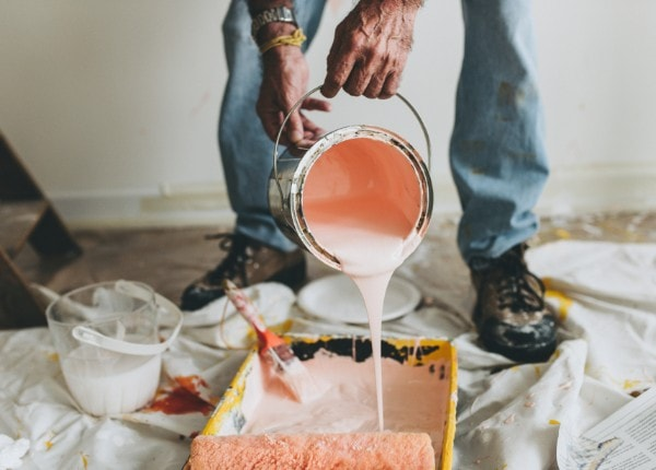 Soft pink paint being poured by a professional contractor